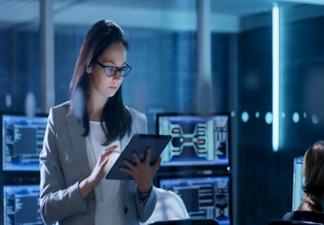 A cybersecurity team member with a tablet works on critical infrastructure protection.