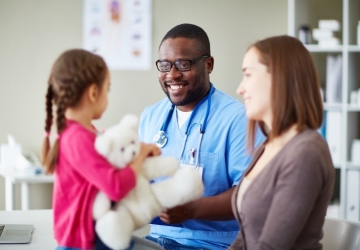 Nurse practitioner smiling with patients in a medical office.