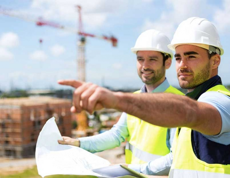 A construction manager and worker at a construction site.