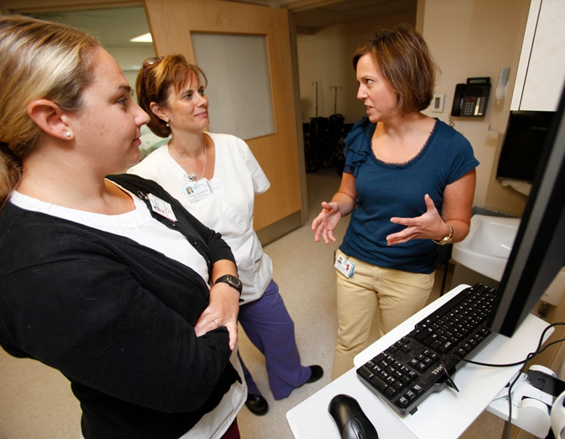 A nurse leader meets with staff in a hospital office.