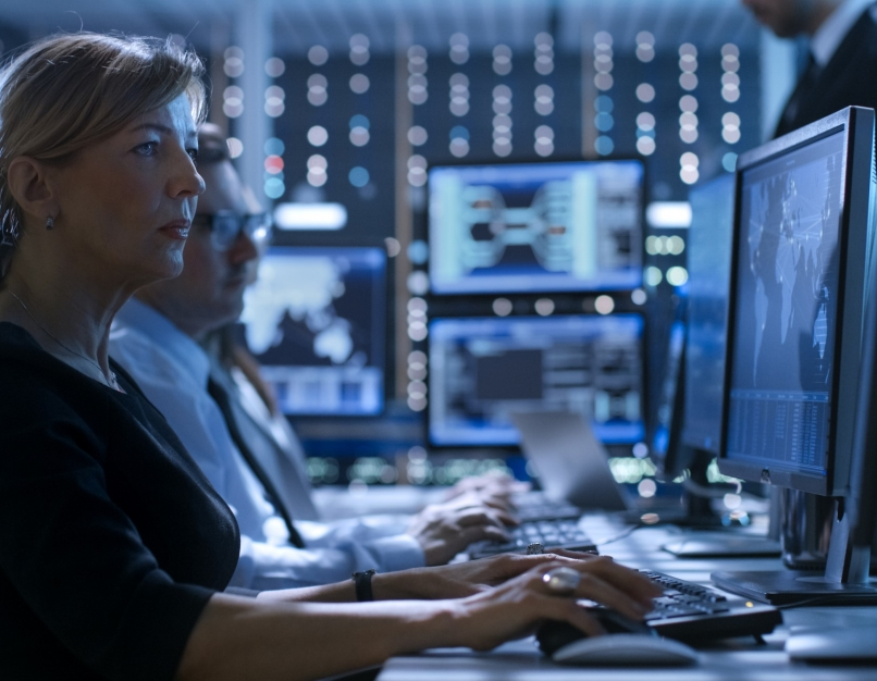 A penetration tester works at a desk among other cybersecurity professionals.
