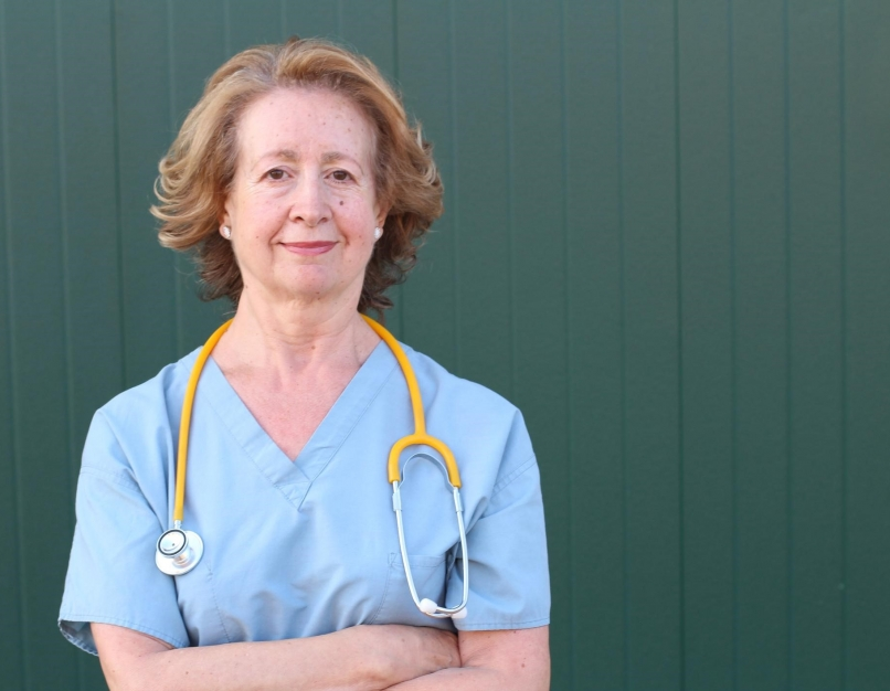 A nurse manager standing with arms folded.