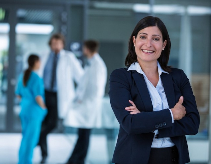 A chief nursing officer smiles while a medical team meets in the background.