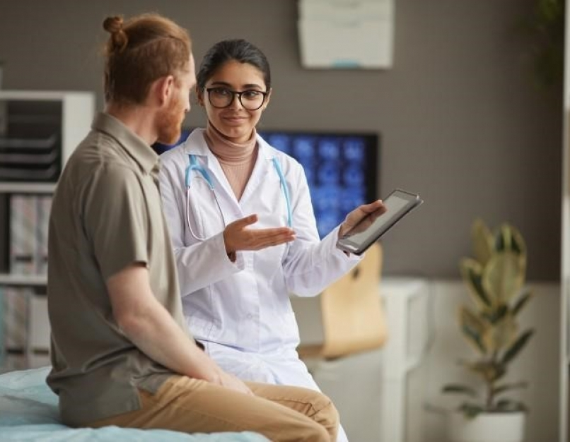 A nurse holding a tablet is discussing test results with a patient.