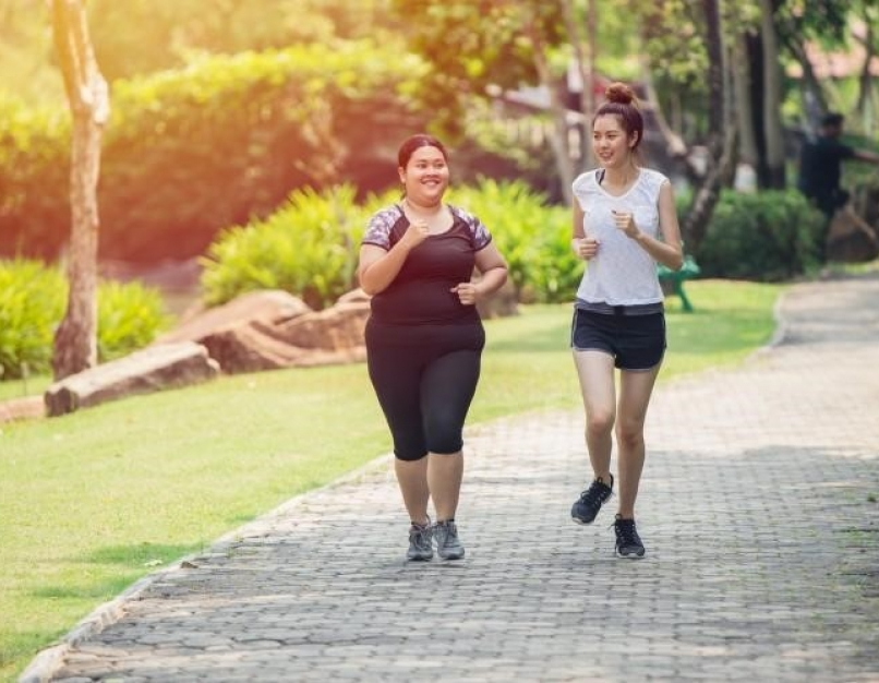 Two young women jog in a park as part of a regular exercise routine, which can help prevent obesity.