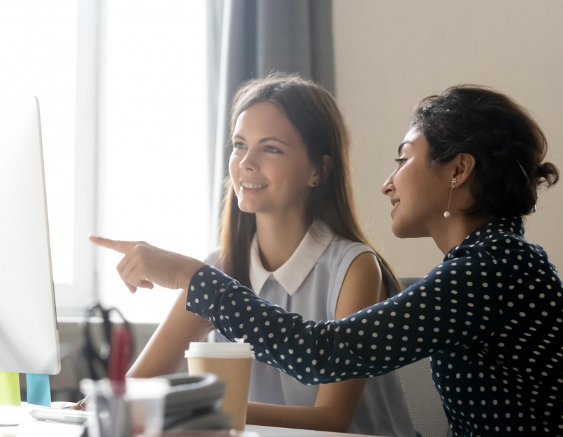 A human resources business partner working with a new employee at her desk.