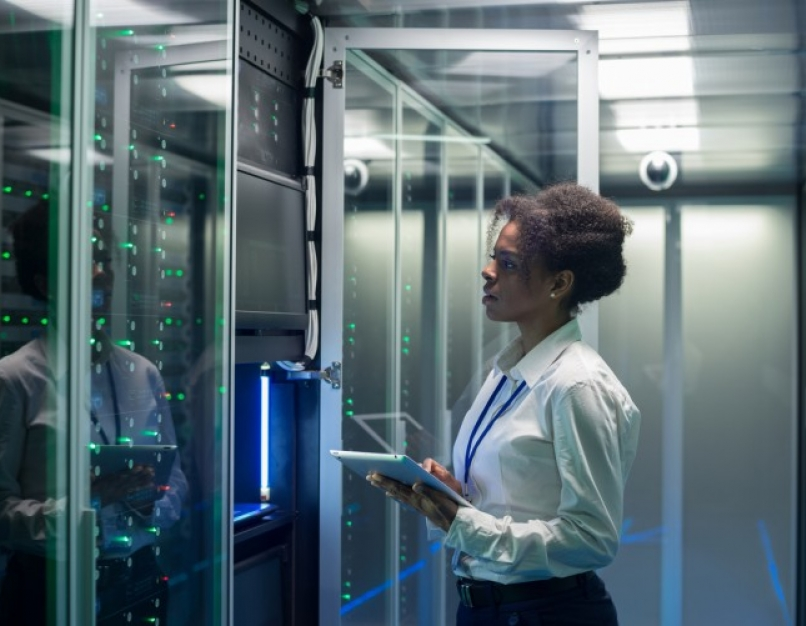 A cybersecurity professional works on a tablet in a data center