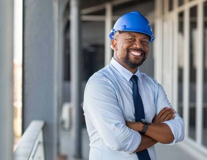 A smiling construction project manager at a building site.